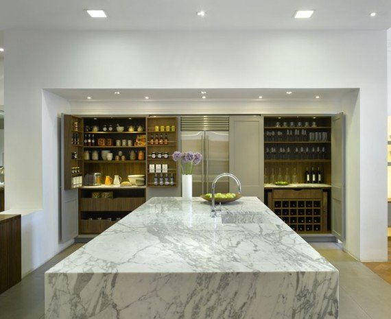 A modern marble marvel, high on drama with gorgeous cupboards providing unique storage options from the bar to the coffee station in this British bespoke kitchen.