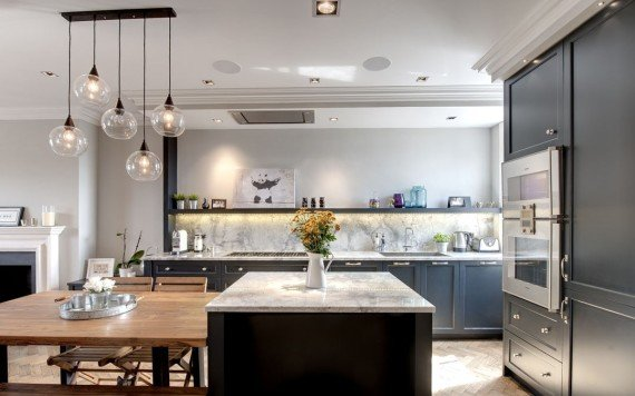 A lagoon stone worktop is matched with a tall splashback, creating a timeless look in this British bespoke kitchen.