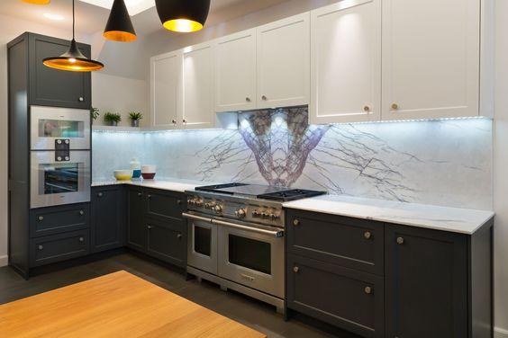 Sleek and distinctive, this urban British bespoke kitchen includes book matched marble and custom pendants in varying shapes.
